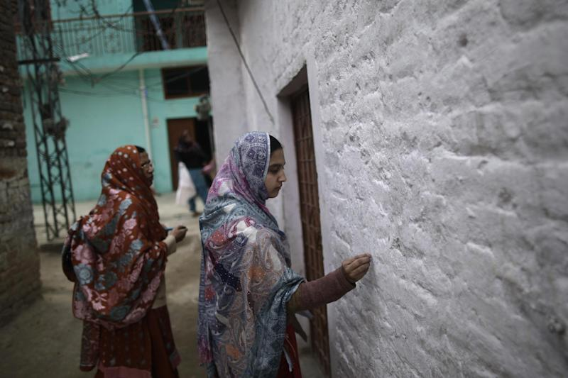 Pakistani health worker Irba Allahdad, 23, right, marks a wall of a home after giving a child living there a polio vaccine, in a neighborhood in Islamabad, Pakistan, Wednesday, Jan. 30, 2013. Some Islamic militants oppose the vaccination campaign, accuse health workers of acting as spies for the U.S. and claim the polio vaccine is intended to make Muslim children sterile. Pakistan is one of the few remaining places where polio is still rampant. (AP Photo/Muhammed Muheisen)