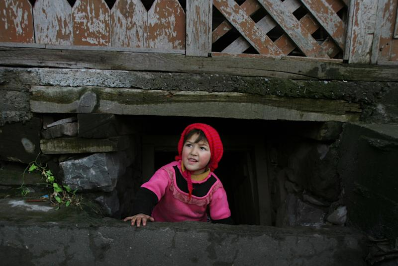 In this Saturday, Jan. 19, 2013 photo, a Pakistani Kashmiri girl looks out from a bunker under her house at the border town of in Chakoti, 60 kilometers (37 miles) South of Muzaffarabad, capital of Pakistani Kashmir. Villagers are building bunkers, bracing themselves for more clashes in Kashmir along a fragile line of control that divides Pakistan and Indian after soldiers on both sides were killed in one of the worst flare-ups in tension in a decade. (AP Photo/M.D. Mughal)