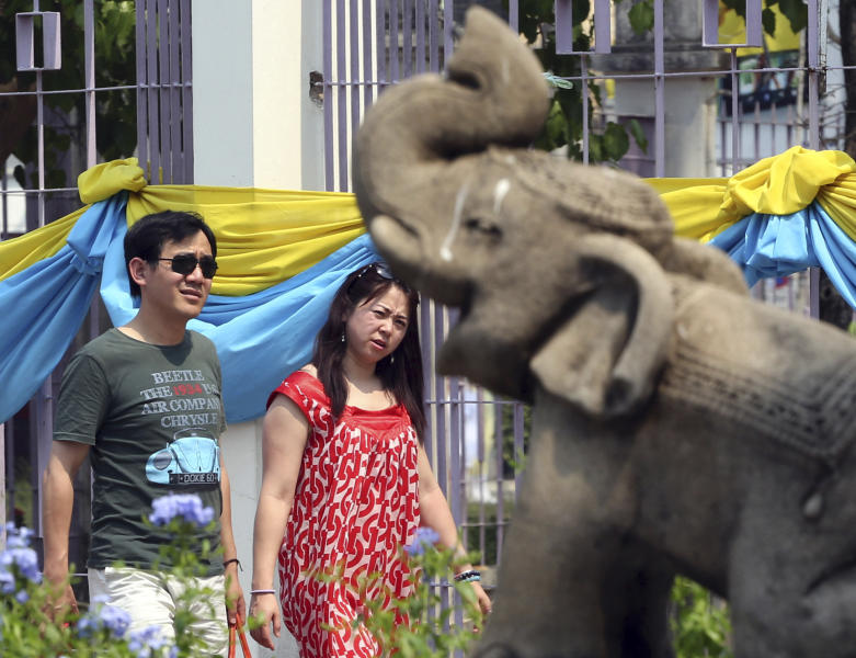 "In this March 30, 2014 photo, a couple of Chinese tourists walks past a stone carving elephant as they enter for a tour at Chiang Mai University in Chiang Mai province, northern Thailand. The bucolic, once laid-back campus of one of Thailand's top universities is under a security clampdown. Not against a terrorist threat, but against Chinese tourists. Thousands have clambered aboard student buses at the university, made a mess in cafeterias and sneaked into classes to attend lectures. Someone even pitched a tent by a picturesque lake. The reason: ""Lost in Thailand,"" 2012 slapstick comedy partly shot on campus that is China's highest-grossing homegrown movie ever. (AP Photo/Apichart Weerawong)"