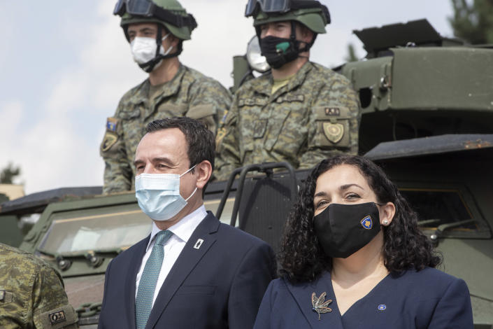 Kosovo president Vjosa Osmani, right, joined by prime minister Albin Kurti, left pose in front of Kosovo Security Force soldiers on top of armored security vehicle donated by U.S during a handout ceremony in the military barracks Adem Jashari in capital Pristina on Monday, Aug. 30, 2021. U.S as the main suppliers of Kosovo's defense the U.S donated 55 armored security vehicles to Kosovo Army. (AP Photo/Visar Kryeziu)