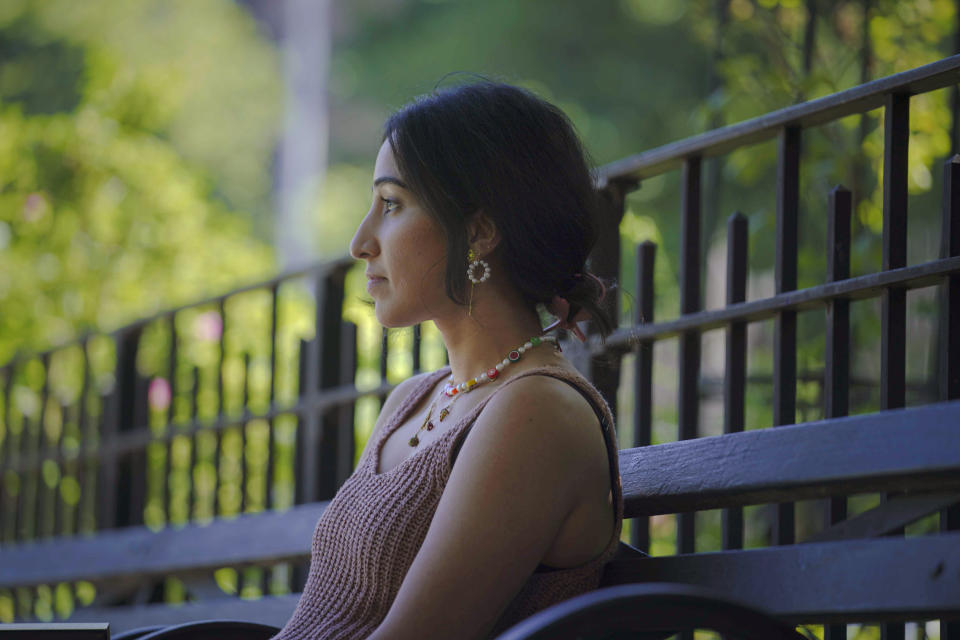 """Noreen Wasti sits in a park near her home, Thursday June 24, 2021, in Brooklyn, N.Y. Wasti lost her father Salman Wasti, 76, a retired biology professor from Glocester, R.I., the day after Christmas last year to COVID-19 and is having a hard time going on. """"This has been the first time I've lost someone so dear to me, so I never had a map for grief nor really understood the magnitude."""" (AP Photo/Bebeto Matthews)"""
