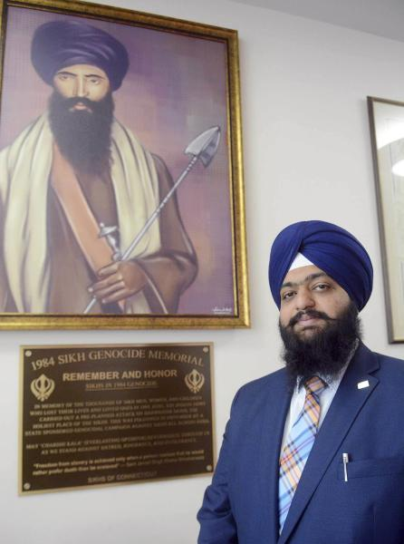 In this May, 29, 2019 photo, Swaranjit Singh Khalsa poses with the newly installed 1984 Sikh Genocide Memorial plaque at Otis Library in Norwich, Conn. The Connecticut library has removed the memorial to Sikhs killed in India 35 years ago after a protest call from the Indian Consulate in New York. (John Shishmanian/NorwichBulletin.com via AP)