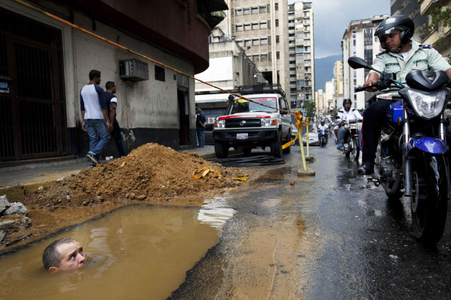 <p>A worker is seen partially submerged under water as he tries to repair a broken pipe in Caracas, Venezuela, Sept. 26, 2012. (Photo: Rodrigo Abd/AP) </p>