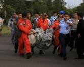 Members of the Search and Rescue Agency SARS carry debris recovered from the sea presumed from missing Indonesia AirAsia flight QZ 8501 at Pangkalan Bun, Central Kalimantan, December 30, 2014 in this photo taken by Antara Foto. REUTERS/Antara Foto/Kenarel