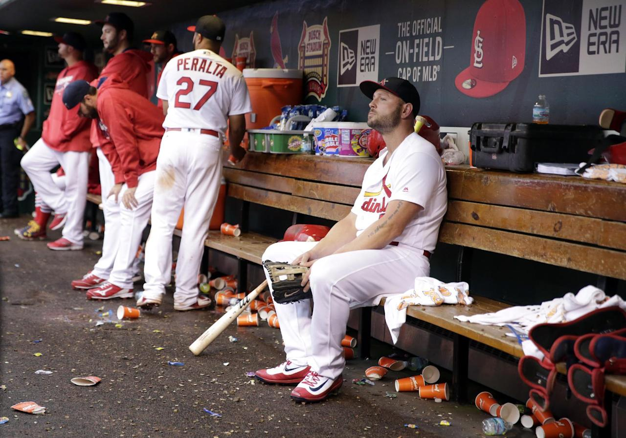 St. Louis Cardinals left fielder Matt Holliday, right, sits in the dugout after leaving a baseball game against the Pittsburgh Pirates during the ninth inning, Sunday, Oct. 2, 2016, in St. Louis. The Cardinals won 10-4 but were eliminated from playoff contention after the San Francisco Giants defeated the Los Angeles Dodgers earlier. (AP Photo/Jeff Roberson)