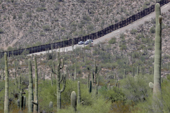 FILE - In this Aug. 22, 2019, file photo, U.S. Customs and Patrol agents sit along a section of the international border wall that runs through Organ Pipe National Monument in Lukeville, Ariz. After a record hot and dry summer, more deaths among border-crossers have been documented in Arizona's desert and mountains. (AP Photo/Matt York, File)