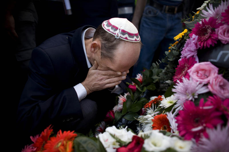 An Israeli man covers his face as he mourns during the funeral of Haifa police chief Ahuva Tomer, in the northern Israeli city of Haifa, Monday, Dec. 6, 2010. Tomer, Israel's top policewoman, who had clung to life for four days after her patrol car was trapped in a burning Israel forest, died Monday of her wounds. (AP Photo/Tara Todras-Whitehill)