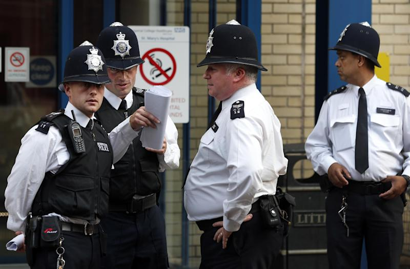 British police officers discuss outside St. Mary's Hospital exclusive Lindo Wing in London, Monday, July 22, 2013. Buckingham Palace officials say Prince William's wife, Kate, has been admitted to the hospital in the early stages of labour. Royal officials said that Kate travelled by car to St. Mary's Hospital in central London. Kate _ also known as the Duchess of Cambridge _ is expected to give birth in the private Lindo Wing of the hospital, where Princess Diana gave birth to William and his younger brother, Prince Harry.The baby will be third in line for the British throne _ behind Prince Charles and William _ and is anticipated eventually to become king or queen. (AP Photo/Lefteris Pitarakis)