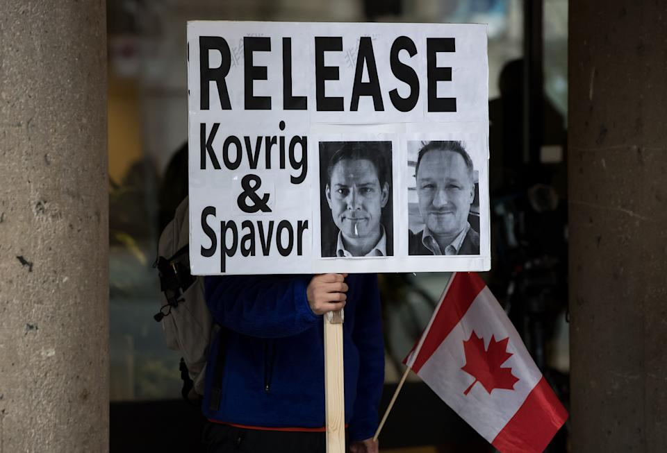 A young man holds a sign bearing photographs of Michael Kovrig and Michael Spavor outside B.C. Supreme Court where Huawei chief financial officer Meng Wanzhou was attending a hearing, in Vancouver on Jan. 21, 2020. (Photo: CP/Darryl Dyck)