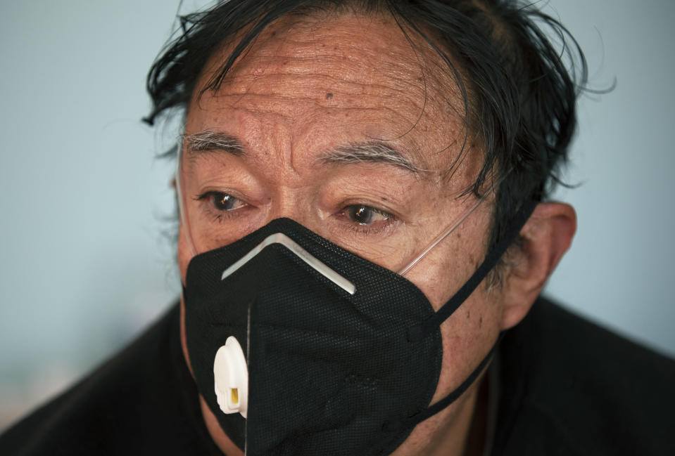 Juan Jose Ledesma, 68, gets teary eyed as he talks about his treatment for COVID-19 in his bedroom where he is isolating, as his son sets up a refill of his oxygen tank in Mexico City, Thursday, Dec. 31, 2020. (AP Photo/Marco Ugarte)