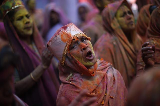 Widows daubed in colours sing during Holi celebrations organised by non-governmental organisation Sulabh International at a widows' ashram in Vrindavan in the northern Indian state of Uttar Pradesh March 17, 2014. Traditionally in Hindu culture, widows are expected to renounce earthly pleasure so they do not celebrate Holi. But women at the shelter for widows, who have been abandoned by their families, celebrated the festival by throwing flowers and coloured powder. Holi, also known as the Festival of Colours, heralds the beginning of spring and is celebrated all over India. REUTERS/Adnan Abidi (INDIA - Tags: SOCIETY RELIGION)