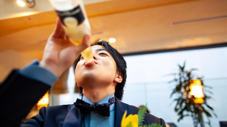 A young Japanese man is drinking beer.
