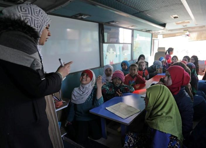 Sudents attend a class inside a bus in the city of al-Bab