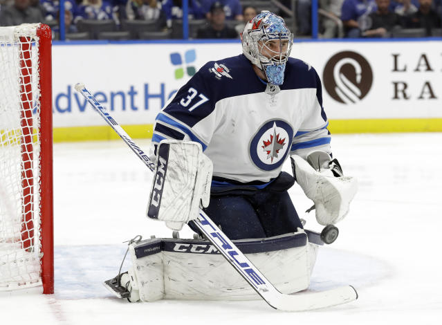 Winnipeg Jets goaltender Connor Hellebuyck makes a save on a shot by the Tampa Bay Lightning during the second period of an NHL hockey game Tuesday, March 5, 2019, in Tampa, Fla. (AP Photo/Chris O'Meara)