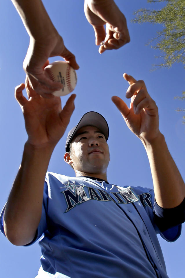 Seattle Mariners pitcher Yusei Kikuchi, from Japan, signs autographs during spring training baseball practice Tuesday, Feb. 12, 2019, in Peoria, Ariz. (AP Photo/Charlie Riedel)