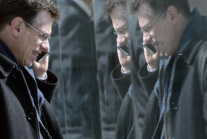 In this Tuesday, Feb. 26, 2013, file photo, a man is reflected in paneling as he speaks on his phone at the Mobile World Congress, the world's largest mobile phone trade show, in Barcelona, Spain. A Spanish newspaper published a document Monday that it said shows the U.S. National Security Agency spied on more than 60 million phone calls in Spain in one month alone — the latest revelation about alleged massive U.S. spying on allies. (AP Photo/Manu Fernandez, File)