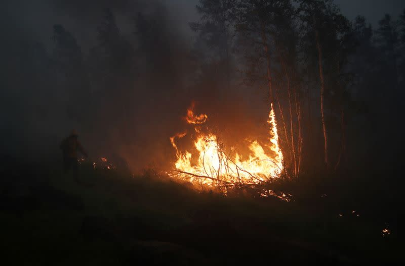 A firefighter works to extinguish a forest fire in Yakutia