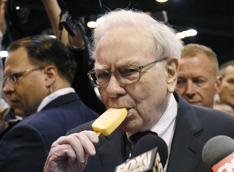 Berkshire Hathaway CEO Warren Buffett bites into an ice cream during a trade show at the company's annual meeting in Omaha, Nebraska May 3, 2014. Warren Buffett's Berkshire Hathaway Inc on Friday said quarterly profit declined 4 percent, falling short of analyst forecasts, as earnings from insurance underwriting declined and bad weather disrupted shipping at its BNSF Railway unit. REUTERS/Rick Wilking (UNITED STATES - Tags: BUSINESS TPX IMAGES OF THE DAY)