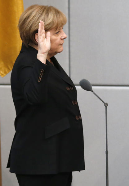 German Chancellor Angela Merkel, left, takes the oath of office during a meeting of the German federal parliament, Bundestag, in Berlin, Germany, Tuesday, Dec. 17, 2013. (AP Photo/Michael Sohn)