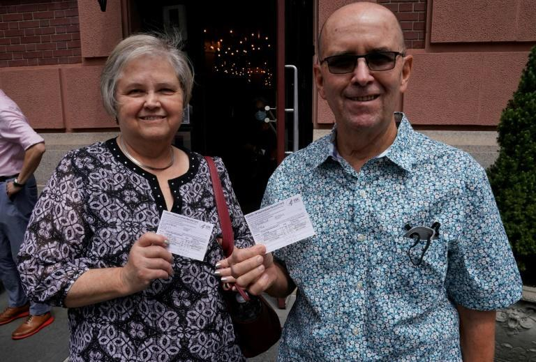 Alton Thibodeaux and his wife Jean hold their vaccination cards outside a restaurant in New York on August 17, 2021