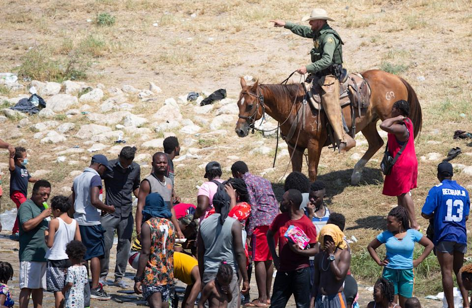 U.S. Border Patrol agents deter Haitians from returning to the USA on the bank of the Rio Grande after migrants crossed back to Mexico for food and water.