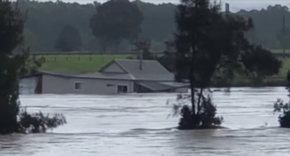 The couple's house is seen floating in the flooded Manning River in Taree.
