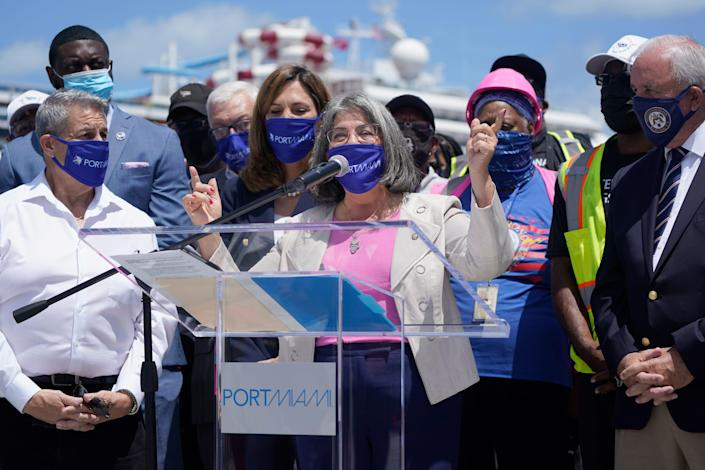 Miami-Dade County Mayor Daniella Levine Cava speaks April 9, 2021, at a podium alongside port workers and elected officials asking for the CDC and the federal government to allow the return of cruising. Carnival Cruise Line's Carnival Horizon cruise ship sits docked behind them at PortMiami in Miami.