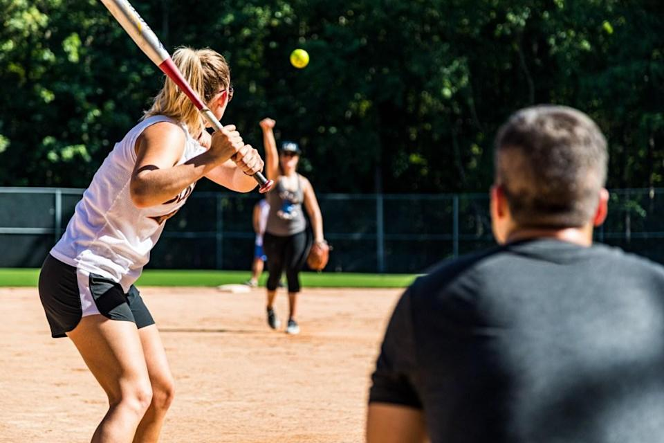 Summer afternoon co-ed softball game at the park