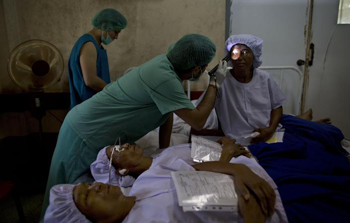 """In this Oct. 22, 2013 photo, an anesthetist inspects the eyes of Saw Min ahead of a cataract operation at a government hospital in Bago, Myanmar. Saw Min waited with hundreds of Myanmar's poorest villagers to be prepped for the simple, free surgery she hopes will restore her sight. """"My heart is racing,"""" said the 38-year-old mother of five, who lost all vision in her left eye one year ago and, in the months that followed, all but 20 percent in her right. (AP Photo/Gemunu Amarasinghe)"""