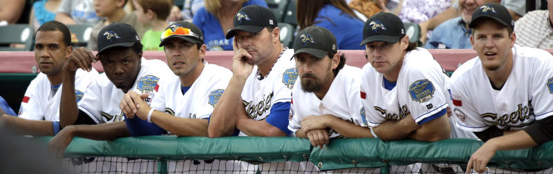 Sugar Land Skeeters pitcher Roger Clemens, center, watches from the dugout with teammates during the first inning of a baseball game against the Bridgeport Bluefish on Friday, Aug. 24, 2012, in Sugar Land, Texas. Clemens, a seven-time Cy Young winner, signed with the Skeeters of the independent Atlantic League this week and is expected to start for the minor league team Saturday at home against Bridgeport. (AP Photo/David J. Phillip)