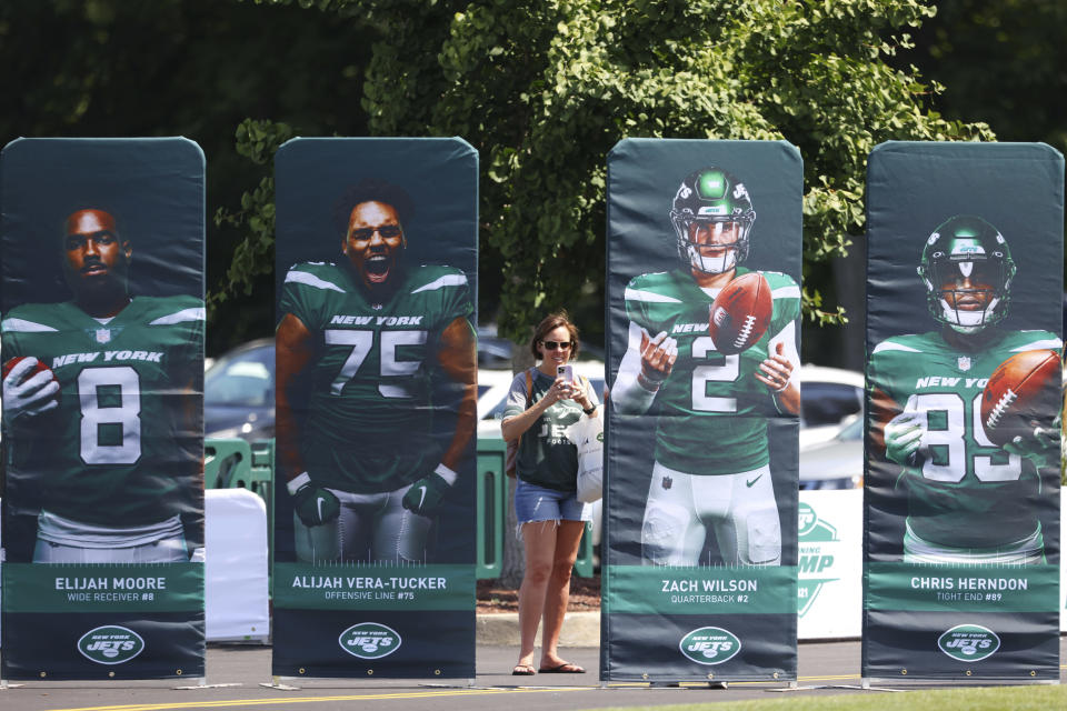 A fan takes a photo behind photos of New York Jets rookies during practice at the team's NFL football training facility, Saturday, July. 31, 2021, in Florham Park, N.J. (AP Photo/Rich Schultz)