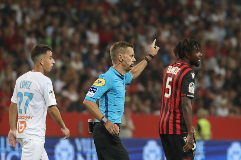 """TOPSHOT - French referee Clement Turpin (C) gestures as he haltes the game after supporters shouted homophobic songs and brandished banners during the French L1 football match between OGC Nice and Olympique de Marseille (OM) on August 28, 2019 at the """"Allianz Riviera"""" stadium in Nice, southeastern France. (Photo by VALERY HACHE / AFP) (Photo credit should read VALERY HACHE/AFP/Getty Images)"""