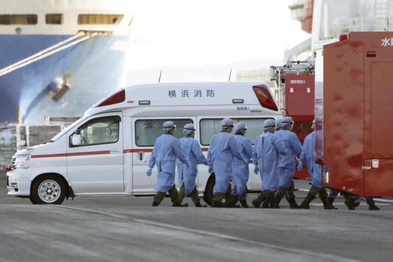 Members of Japan Self Defense Forces walk into the quarantined cruise ship Diamond Princess in the Yokohama Port Sunday, Feb. 9, 2020, in Yokohama, Japan. China's death toll from the new virus outbreak has risen to over 800, surpassing the number of fatalities in the 2002-03 SARS epidemic, as other governments stepped up efforts to block the disease. (AP Photo/Eugene Hoshiko)
