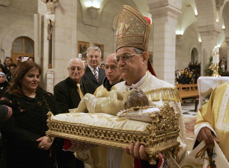 Latin Patriarch of Jerusalem Fouad Twal  carries the statuette of baby Jesus during the Christmas midnight Mass at the Church of the Nativity, traditionally believed to be the birthplace of Jesus Christ, in the West Bank town of Bethlehem early Sunday, Dec. 25, 2011. (AP Photo/Majdi Mohammed, Pool)
