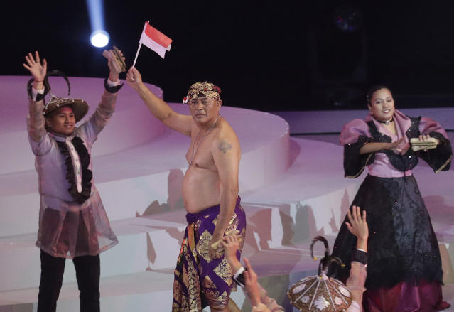 A member of the Indonesian delegates waves a flag during the opening ceremony of the 30th South East Asian Games at the Philippine Arena, Bulacan province, northern Philippines on Saturday, Nov. 30, 2019. (AP Photo/Aaron Favila)
