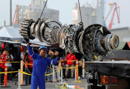 A worker assists his colleague as an turbine engine of Lion Air flight JT610 is lifted up at Tanjung Priok port in Jakarta