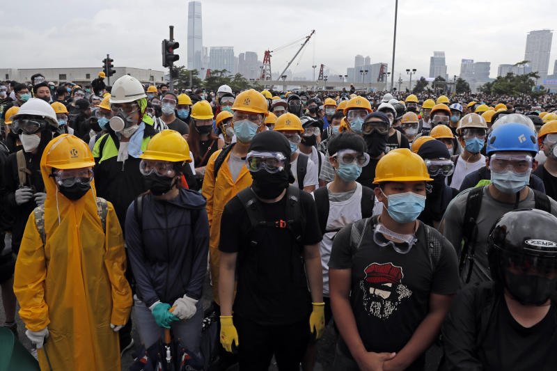 In this photo taken on Wednesday, June 12, 2019, protestors wear masks and helmets to protect their identities near the Legislative Council in Hong Kong. Young Hong Kong residents protesting a proposed extradition law that would allow suspects to be sent to China for trial are seeking to safeguard their identities from potential retaliation by authorities employing mass data collection and sophisticated facial recognition technology. (AP Photo/Kin Cheung)