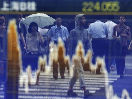 Passers-by are reflected on a graph showing movements of Shanghai B shares outside a brokerage in Tokyo