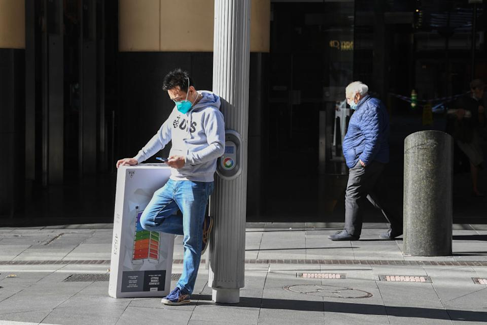 A man wears a face mask whilst on his mobile phone after collecting a last minute product in the CBD in Sydney, Australia.