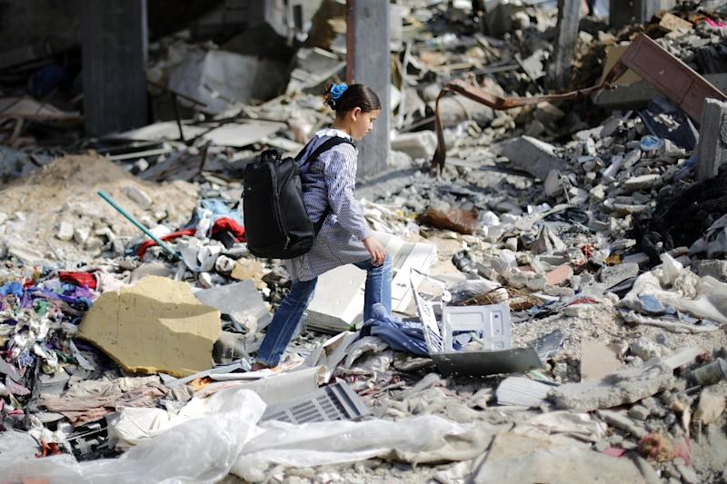A Palestinian girl makes her way though the rubble of destroyed buildings as she heads home from school on March 11, 2015 in Beit Hanun, northern Gaza