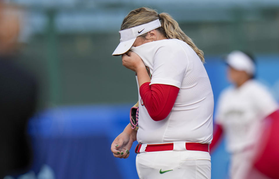 Mexico's pitcher Dalla Escobedo wipes the sweat from her face during the softball game between Mexico and Canada at the 2020 Summer Olympics, Wednesday, July 21, 2021, in Fukushima , Japan. (AP Photo/Jae C. Hong)