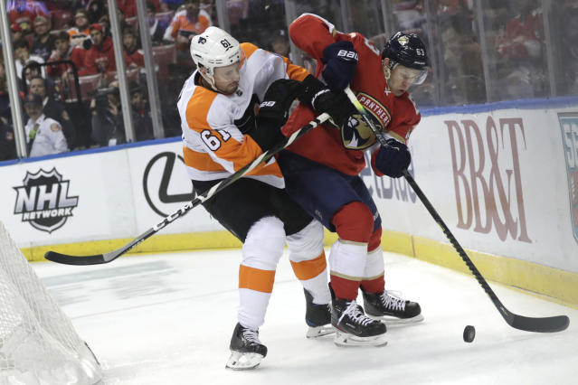 Philadelphia Flyers defenseman Justin Braun (61) and Florida Panthers right wing Evgenii Dadonov (63) go for the puck during the first period of an NHL hockey game Thursday, Feb. 13, 2020, in Sunrise, Fla. (AP Photo/Lynne Sladky)