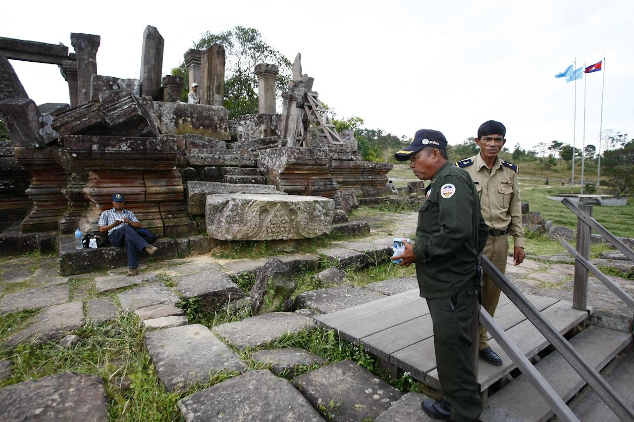 A temple guard, right, talks with a military police, center, at an entrance of the famed Preah Vihear temple near Cambodia-Thai border in Preah Vihear Province, Cambodia, Sunday, Nov. 10, 2013. The International Court of Justice rules on a dispute between Cambodia and Thailand over land surrounding the 1,000-year-old temple on Monday. (AP Photo/Heng Sinith)