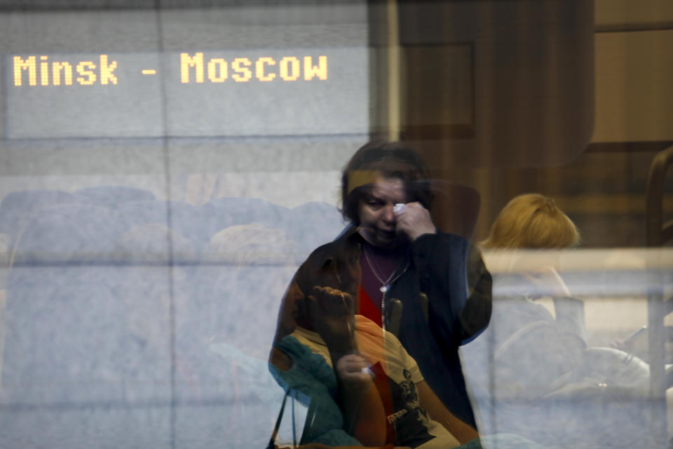 A woman wipes tears as she is reflected on a train car in Minsk, Belarus, on Friday, May 28, 2021, as a relative heads for Moscow. After a Ryanair jet was diverted to Minsk on Sunday, May 23, 2021, where a dissident journalist was arrested, the European Union banned flights from Belarus. Now, those who want to leave the country are finding themselves with few options. (AP Photo)