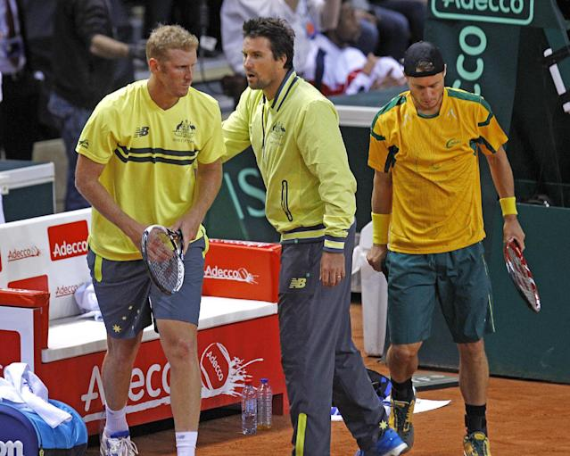Australian team captain Patrick Rafter, center, encourages his players Lleyton Hewitt, right, and Chris Guccione during their doubles match against French pair Jo-Wilfried Tsonga and Richard Gasquet, in the first round of the Davis Cup between France and Australia, in La Roche sur Yon, western France, Saturday Feb. 1, 2014. (AP Photo/Remy de la Mauviniere)