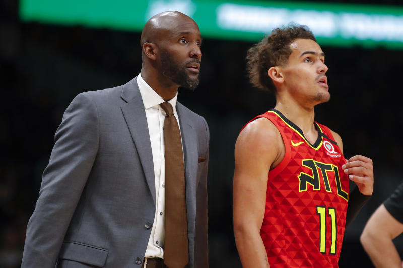 Head coach Lloyd Pierce speaks with Atlanta Hawks guard Trae Young (11) during the first half of an NBA basketball game against the Washington Wizards on Sunday, Jan. 26, 2020, in Atlanta. (AP Photo/Todd Kirkland)