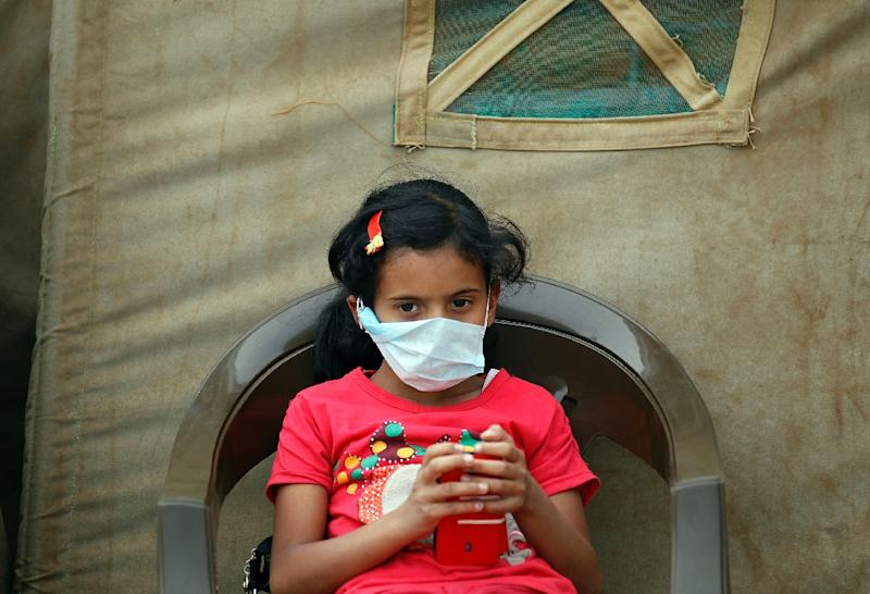 A Yemeni child suspected of being infected with cholera sits outside a makeshift hospital in Sanaa