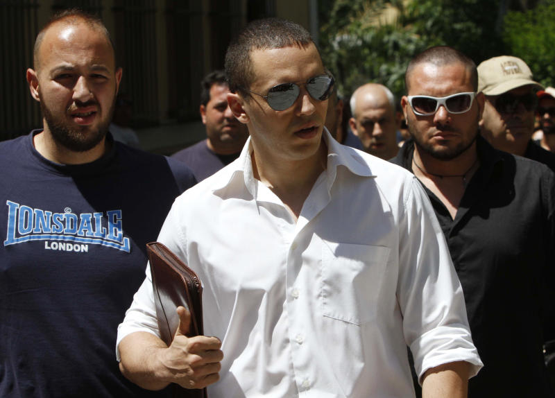 The spokesman of Greece's extreme-right Golden Dawn party Ilias Kasidiaris, center, escorted by party members arrives at the prosecutor's office in Athens, Monday, June, 11, 2012. Kasidiaris who caused uproar last week by hitting one politician and throwing a glass of water over another during a live TV news program, on Monday sued the two candidates and the television channel that hosted the show. He appeared at an Athens court to submit lawsuits against Communist Party candidate Liana Kanelli and Syriza party member Rena Dourou for unprovoked insult and against Antenna television for illegal detention. (AP Photo/Petros Karadjias)
