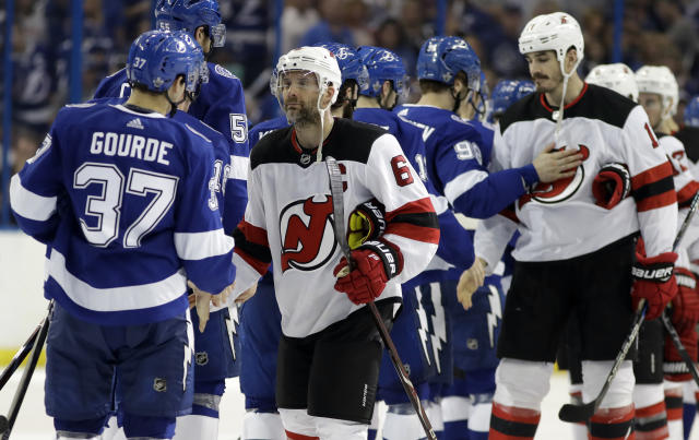 New Jersey Devils defenseman Andy Greene (6) congratulates Tampa Bay Lightning center Yanni Gourde (37) after the Lightning eliminated the Devils during Game 5 of an NHL first-round hockey playoff series Saturday, April 21, 2018, in Tampa, Fla. (AP Photo/Chris O'Meara)