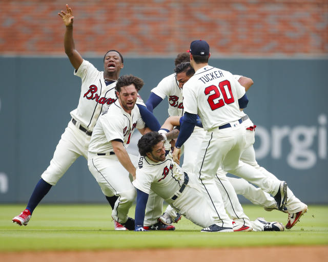 Atlanta Braves Dansby Swanson is tackled by teammates after hitting a game winning, two run single in the ninth inning of a baseball game against the Miami Marlins, Sunday, May 20, 2018, in Atlanta. The Atlanta Braves won the game 10-9. (AP Photo/Todd Kirkland)